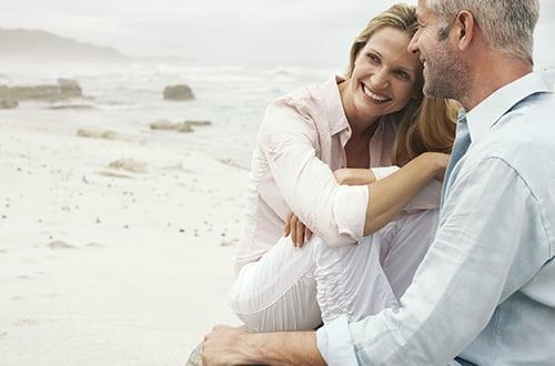 146561927_casal_adulto_praia_sorrindo_sentado